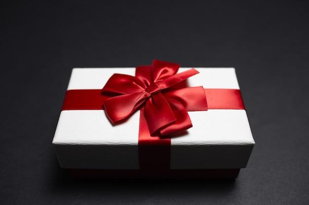 Close-up van witte giftdoos met rode lintboog