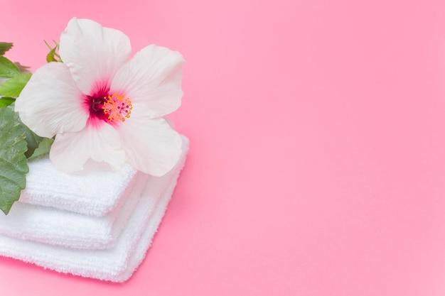 Close-up van witte hibiscusbloem en handdoeken op roze achtergrond