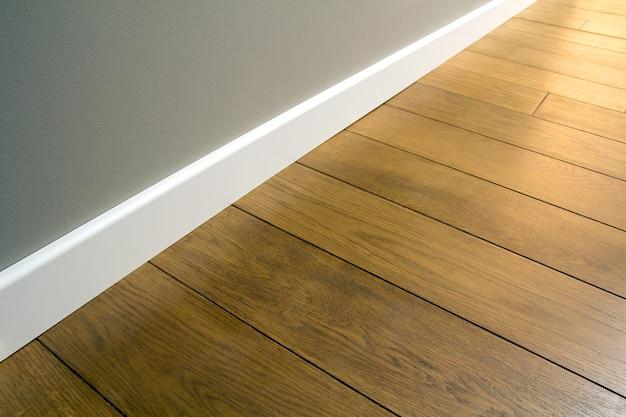 Close up van witte kunststof plinten op donkere houten eiken vloer parket.