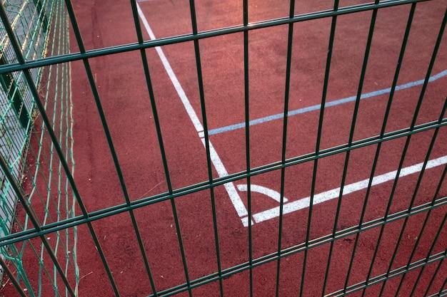 Close-up van witte markering lijnen van outdoor basketbalveld omheind met beschermende metalen hek.
