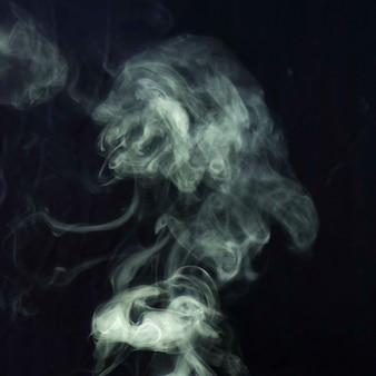 Close-up van witte rook verspreid over een zwarte achtergrond