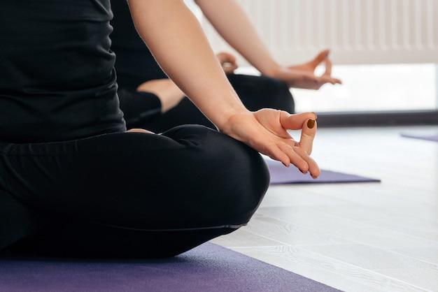 Close-up van yoga vrouwen zitten in lotus asana tijdens yogales, bijgesneden weergave
