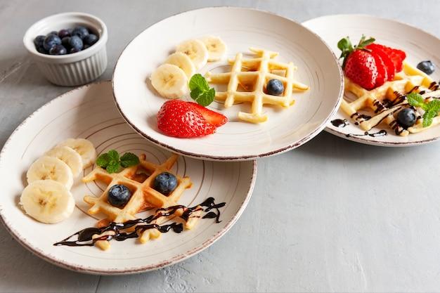 Close-up van zachte weense wafels op de drie platen met bosbessen, aardbei en chocoladesaus