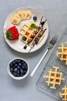 Close-up van zachte weense wafels op de plaat met bosbessen, aardbei en chocoladesaus