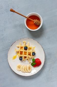Close-up van zachte weense wafels op de plaat met bosbessen, aardbei en honney