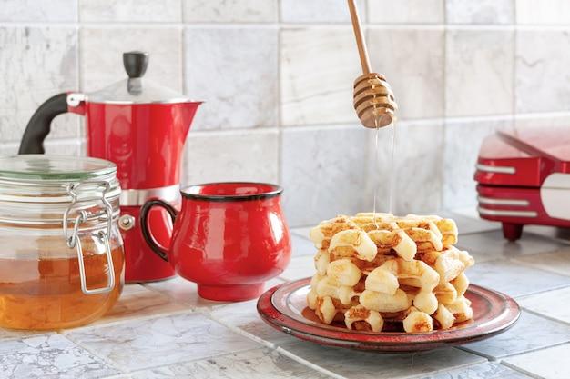 Close-up van zachte weense wafels op de plaat met hete honing.