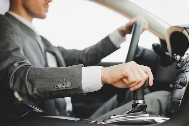 Close-up van zakenman die de auto drijft