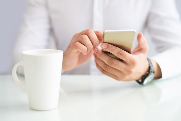 Close-up van zakenman die internet op telefoon doorbladert