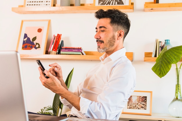 Close-up van zakenman die mobiele telefoon in het bureau met behulp van