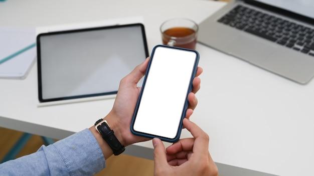 Close-up van zakenman die mobiele telefoon vasthoudt terwijl hij aan een modern bureau zit.