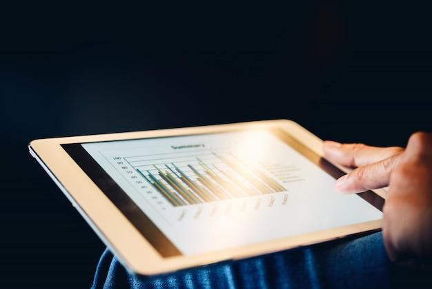 Close-up van zakenman die tablet gebruiken die project in bureau controleren.