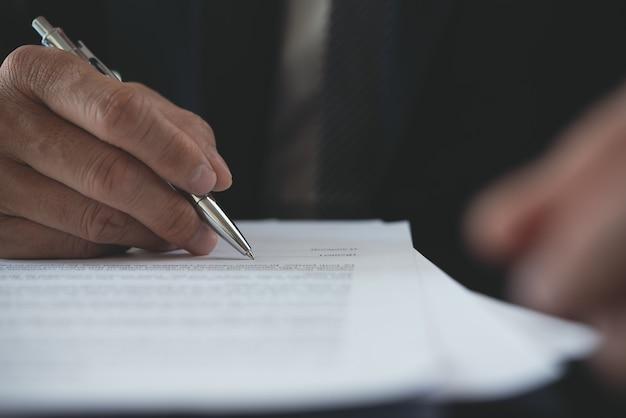 Close-up van zakenman die zakelijk contract ondertekent op kantoor