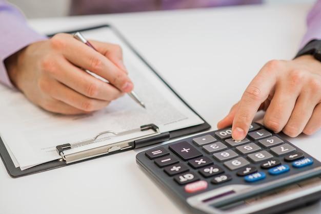 Close-up van zakenman facturen met calculator berekenen