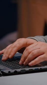 Close-up van zakenman handen op toetsenbord zittend aan bureau tafel in opstarten bedrijf kantoor browsen ec...