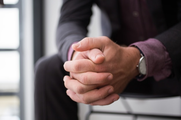 Close-up van zakenman handen zitten op stoel