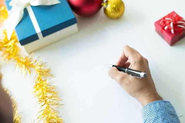 Close-up van zakenman het schrijven giftlijst vóór kerstmis