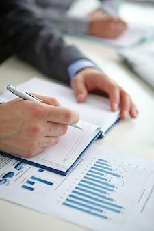 Close-up van zakenman het schrijven van een samenvatting