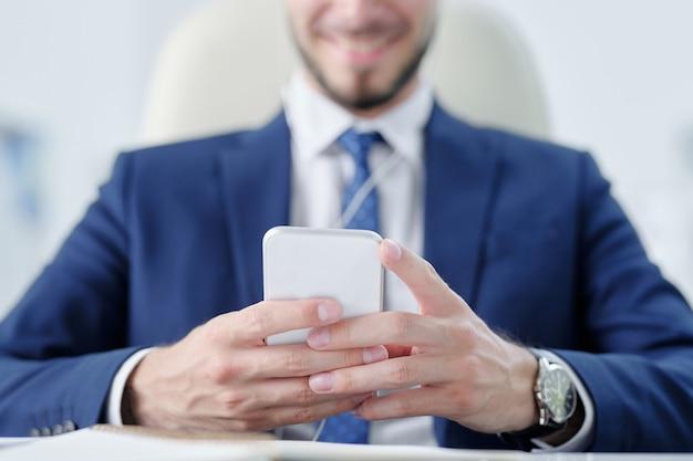 Close-up van zakenman in pak met behulp van smartphone tijdens het sms-bericht naar collega