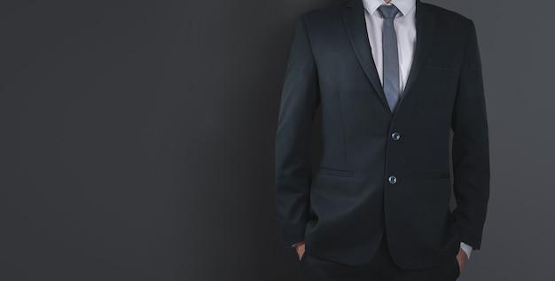 Close-up van zakenman in zwart pak en stropdas, zwarte muur. kopieer ruimte voor reclame.
