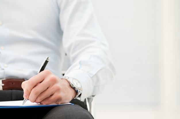 Close-up van zakenman schrijven formulier op klembord op kantoor