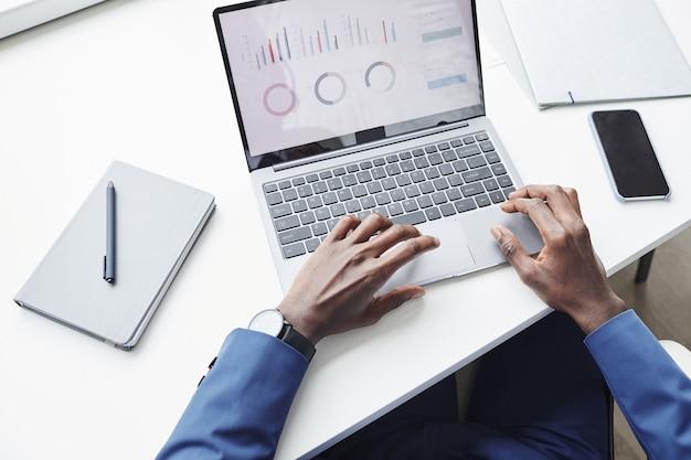 Close-up van zakenman zittend aan de tafel werken met grafieken op laptop online