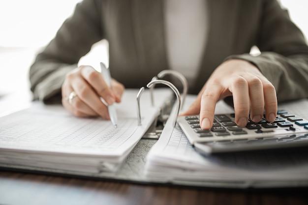 Close-up van zakenmanhand die factuur met calculator berekenen