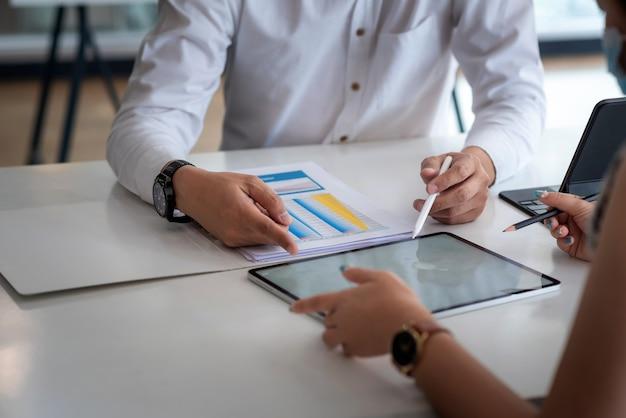 Close-up van zakenmanhanden die werkbesprekingen analyseren die tabletbureaudocumenten gebruiken.