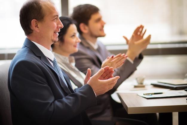 Close-up van zakenmensen die handen klappen. zakelijk seminar concept