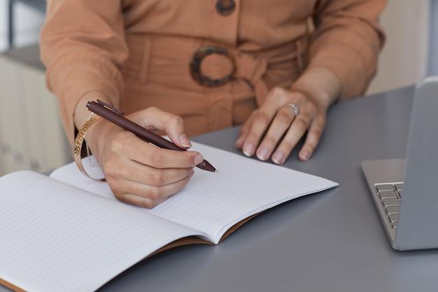 Close-up van zakenvrouw business plannen schrijven in notitieblok werken op haar werkplek