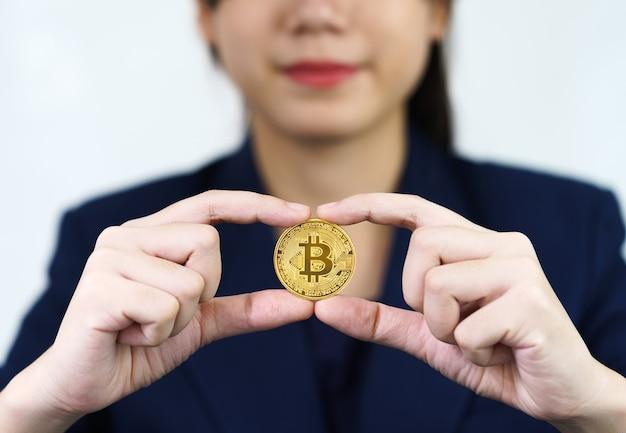 Close-up van zakenvrouw die enkele stukjes gouden bitcoin-token vasthoudt, bitcoin is een van de populaire cryptocurrency