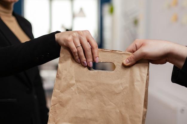 Close up van zakenvrouw die levering van voedsel ontvangt