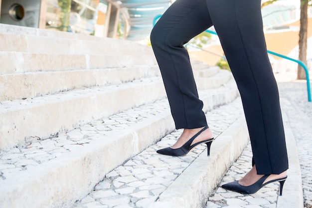 Close-up van zakenvrouw die op trappen beweegt
