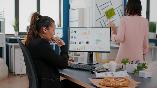 Close-up van zakenvrouw die smakelijke pizza eet terwijl ze financiële statistieken analyseert aan het bureau op de werkplek