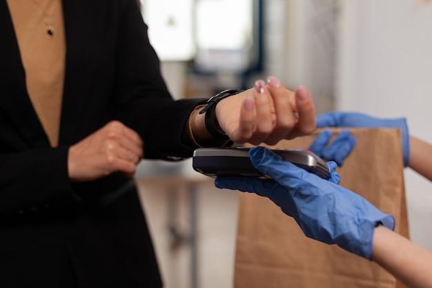 Close-up van zakenvrouw die voedselbestelling betaalt met contactloze betaling met slim horloge