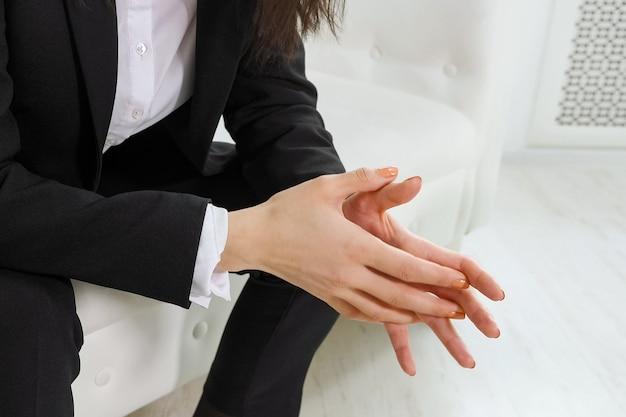 Close-up van zakenvrouw die zenuwachtig handen beweegt voordat ze een psycholoog op kantoor ontmoet.