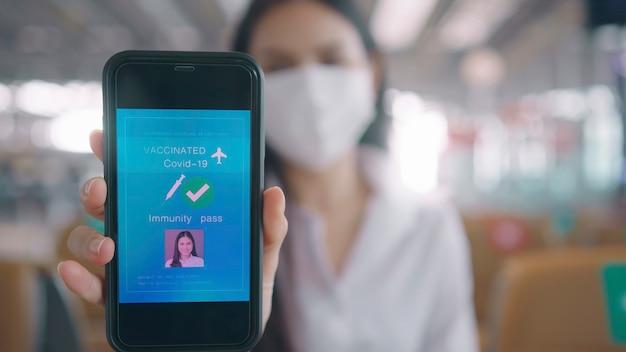 Close up van zakenvrouw draagt beschermend masker in internationale luchthaven, vaccin paspoort op haar smartphone