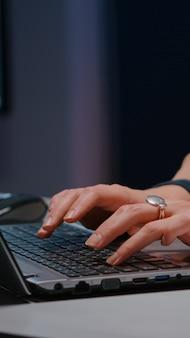 Close-up van zakenvrouw handen op toetsenbord zit aan bureau in opstarten bedrijf kantoor