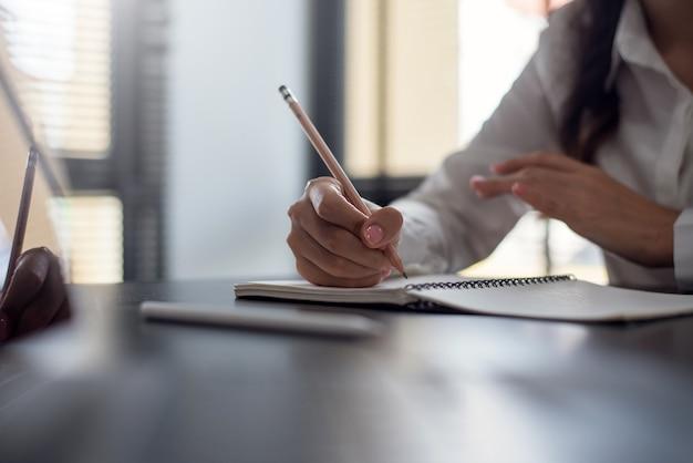 Close up van zakenvrouw maken van aantekeningen in notitieblok op bureau op kantoor