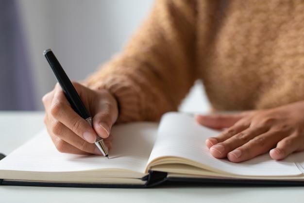 Close-up van zakenvrouw maken van aantekeningen in persoonlijke organizer