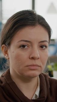 Close up van zakenvrouw met een handicap die verdrietig naar de camera kijkt