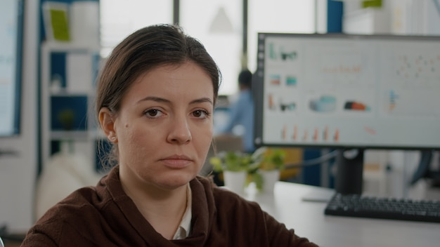 Close-up van zakenvrouw met een handicap die verdrietig naar voren kijkt terwijl een divers team aan een financieel project werkt financial