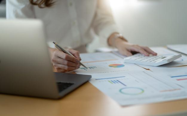 Close up van zakenvrouw of accountant hand met pen bezig met rekenmachine om bedrijfsgegevens, boekhoudingsdocument en laptopcomputer op kantoor, bedrijfsconcept te berekenen.