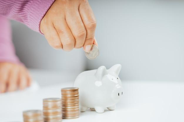 Close-up van zakenvrouwenhand die geldmuntstuk zetten in spaarvarken om geld te besparen. geld besparen en financieel concept