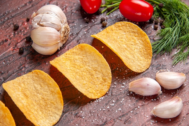 Close-up van zelfgemaakte heerlijke vier knapperige chips rode peper knoflook groene tomaten op donkere achtergrondafbeelding