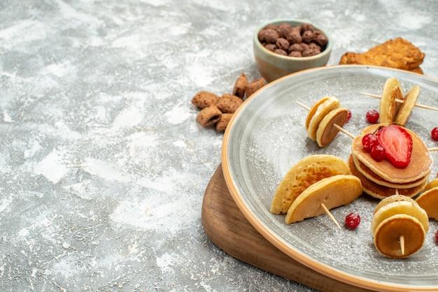 Close-up van zelfgemaakte pannenkoeken en koekjes op houten snijplank op blauw