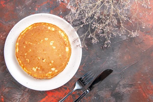 Close-up van zelfgemaakte pannenkoeken op een witte plaat en mes met vork op gemengde kleur
