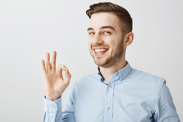 Close-up van zelfverzekerde gelukkige kerel die ok gebaar toont, geen probleem, alles ok, goed werk prijzend, zeg goed gedaan