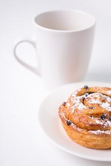 Close up van zoet broodje met rozijnen en kopje koffie of thee op witte achtergrond