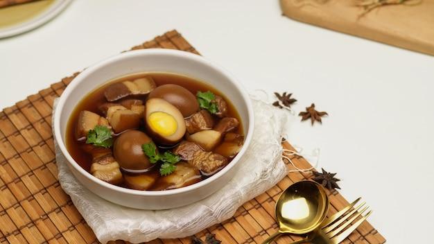 Close-up van zoete bruine gestoofde eieren soep kai palo met varkensvlees