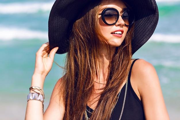 Close-up van zonnige zomer portret van mooie vrouw met pluizige brunette lange haren, glimlachen, plezier maken in de buurt van blauwe oceaan, vintage zonnebril, outfit en hoed dragen, vakantiestijl, felle kleuren